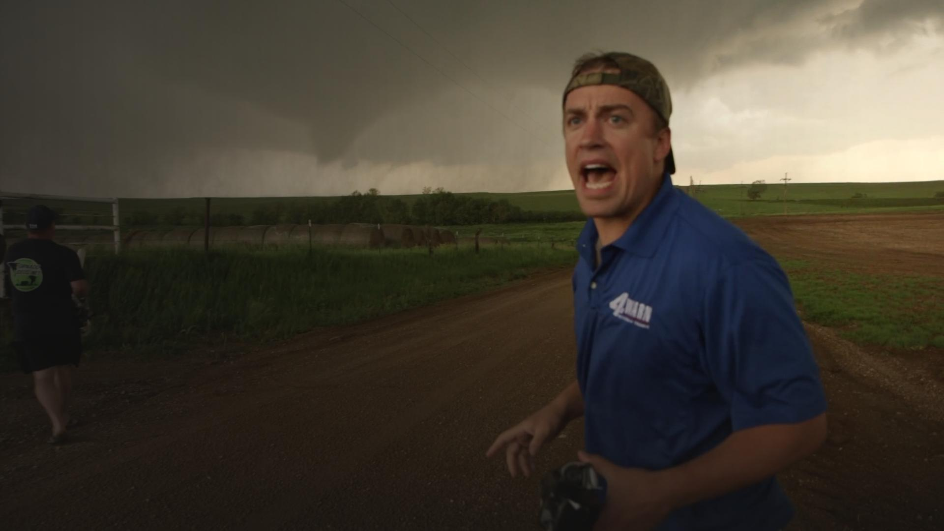A tornado chaser yells at his team as giant tornado cell approaches