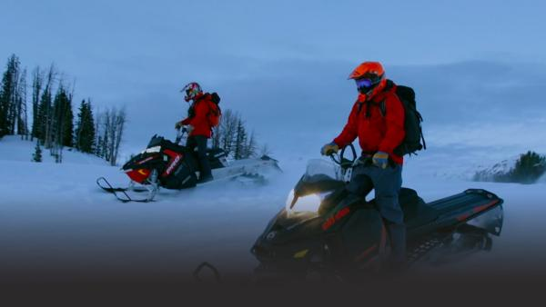Two men ride snowmobiles