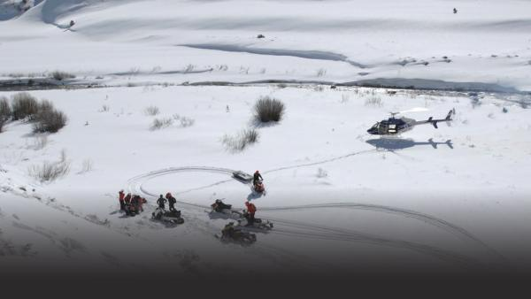 People reach injured person with helicopter and snowmobile