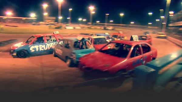 A bunch of Banger cars all piled up in the middle of a race.