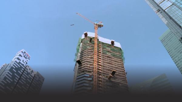 A tower crane lifts a load to the top of highrise construction project
