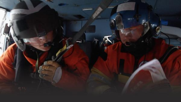 Men in a helicopter looking at maps