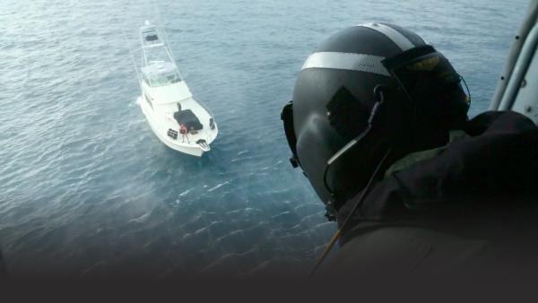 Coast Guardsman looks down on a boat