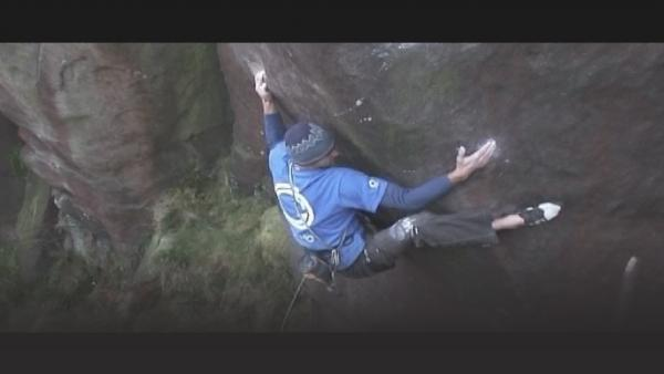 British man trad climbing a vertical cliff