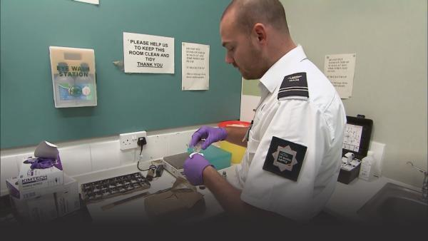 Customs officer performing drug tests.