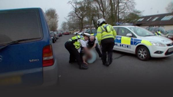 Police try to restrain a man as he resists arrest