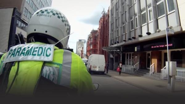 A paramedic on a motorcycle rushes through traffic