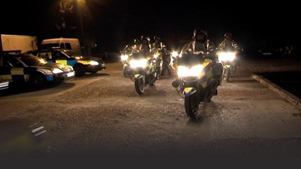 fleet of motorcycle cops exiting a parking lot