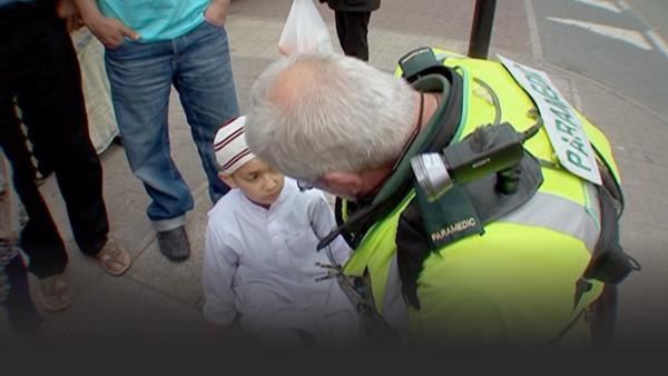 paramedic helps a young boy after he's been hit by a car