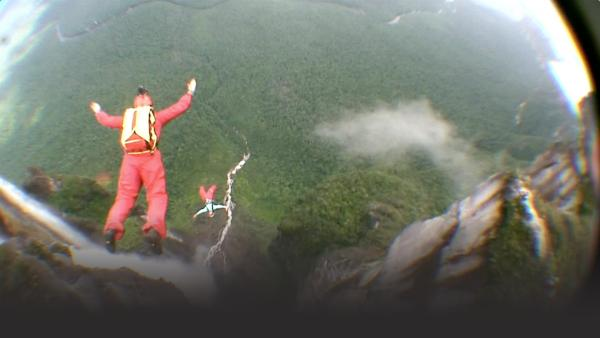 Women base jump off of cliff
