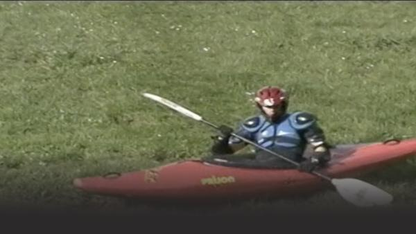 Man in a kayak on some grass