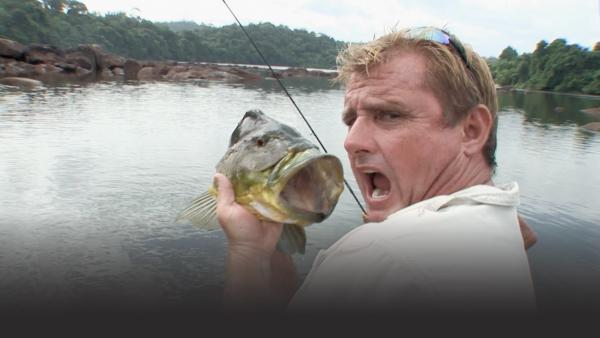 Man holds up a large bass next to his head, imitating the large mouth of the bass