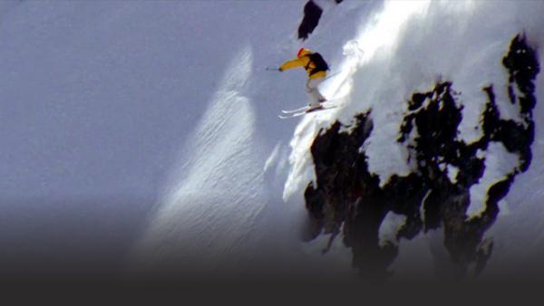 Skier gets set for a jump on a steep slope