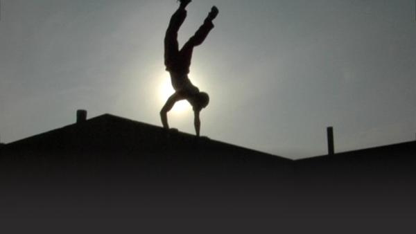 Man practicing parkour balancing on ledge of building