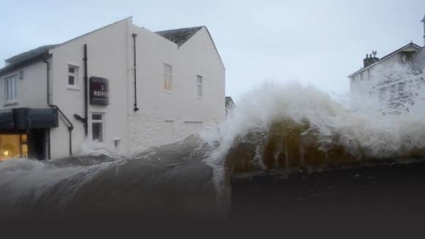 Waves crash over seaside barrier of the Newlyn Bridge in Cornwall
