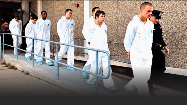 Seven teens do a perp walk in prison jumpsuits