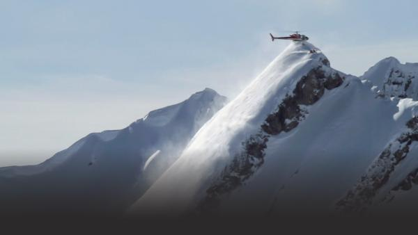 Helicopter drops off several skiers on a mountain peak