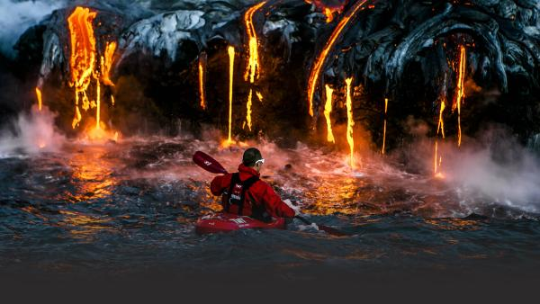 Kayakers paddle next to lava flow in Hawaii