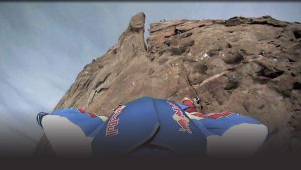 Man jumps of mountain in wing suit