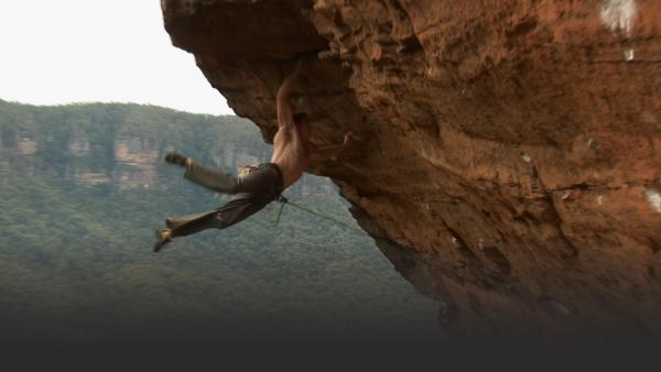 Man climbing has jumps up the cliff to grab above him, both legs swinging out