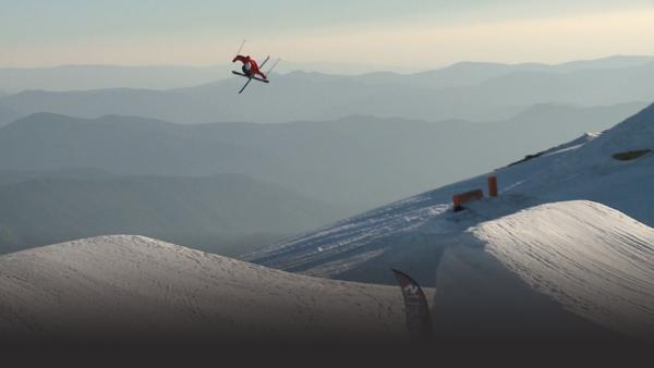 Skier high above a jump, mid twist, mountains in background