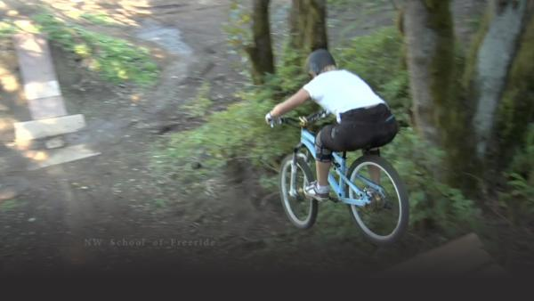 woman on a blue mountain bike leaps off a wooden bridge